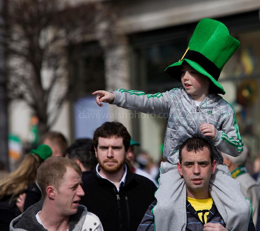 Boy wearing leprechaun hat on man's shoulders, at Dublin St. Patrick's Day parade