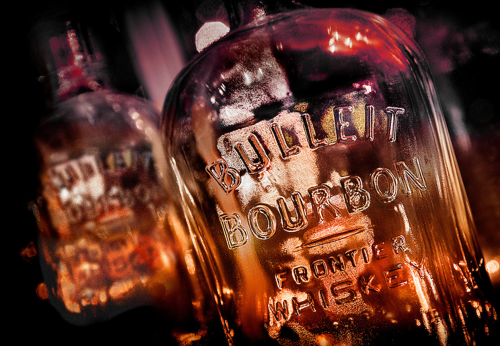 Empty whiskey bottles on a window sill.
