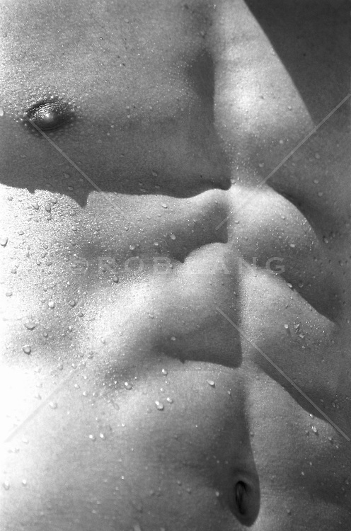Close up of a young mans wet chest and abdomen, (b&w)