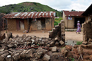 A woman is walking by a destroyed home in Kakuruk village, Gashish district, in the local government of Barkin Ladi, near Jos, Plateau State, Nigeria. The village, inhabited by Christians from the Berom tribe, has received various attacks by neighbouring Muslim Fulani - a nomadic cattle-herder tribe non-indigenous to Plateau - with the last one on 7th July, 2012, when more than 30 houses were demolished and 8 Christian villagers killed.