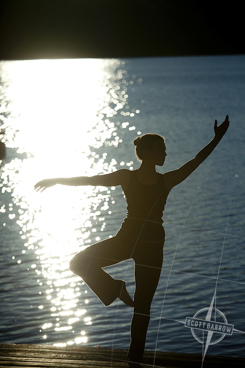 A silhouetted woman doing yoga lakeside at sunrise.