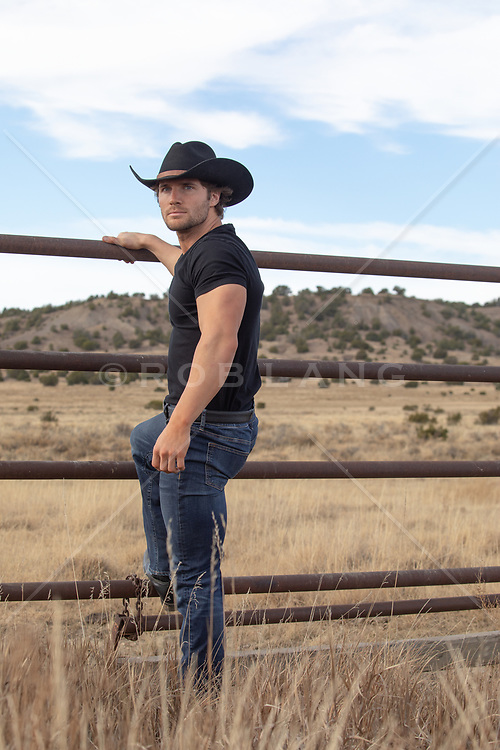 All American cowboy on a rustic fence