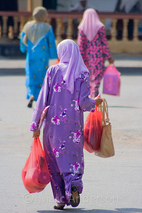 Malaysian Women wearing traditional Islamic dress carrying shopping bags as they walk along a road in Malaysia.