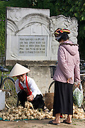 Hilltribe women selling vegetables in front of a monument at the place of French Artillery Commander Pirot's bunker, where he commited suicide after defeat.