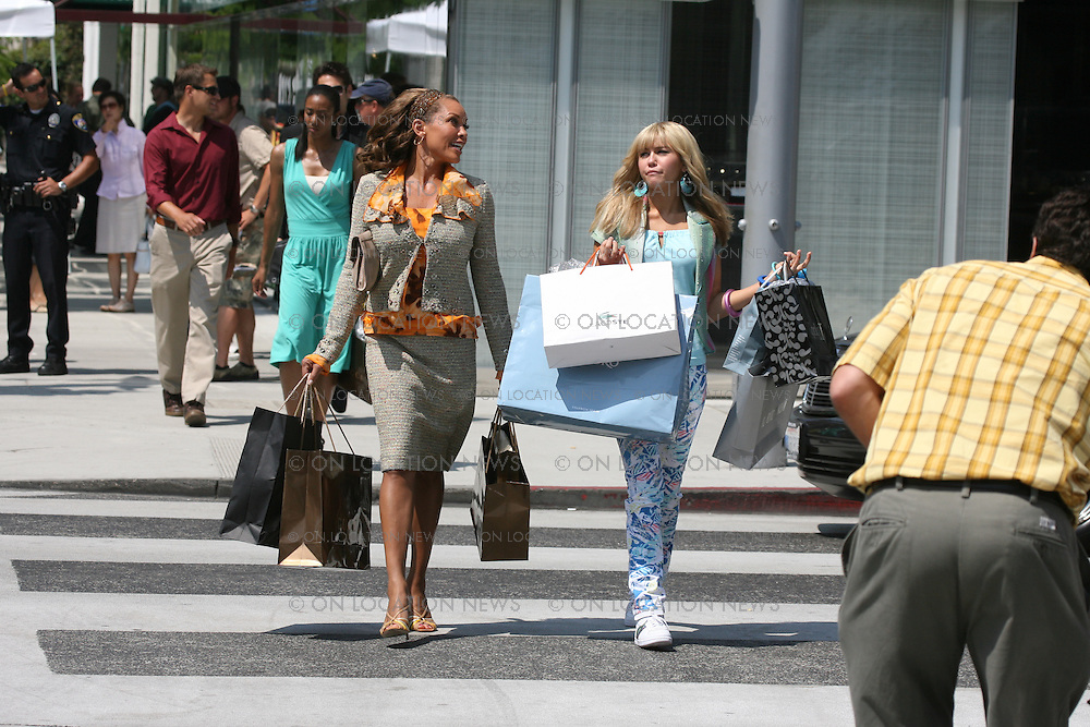 BEVERLY HILLS, CALIFORNIA - MONDAY 14TH JULY 2008 NON EXCLUSIVE: Miley Cyrus shooting scenes for her new movie 'Hannah Montana'. Cyrus was joined on set by Ugly Betty star Vanessa Williams. In this scene Miley went on a shopping spree with Williams on Rodeo Drive and was stopped by a fan for an autograph. Later Vanessa shot a dance sequence in the middle of the street on Rodeo Drive. Photograph: On Location News. Sales: Eric Ford 1/818-613-3955 info@OnLocationNews.com