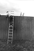 Builder climbing a fence with a ladder, Glastonbury, Somerset, 1989