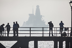© Licensed to London News Pictures. 02/11/2017. Portsmouth, UK.  People watching as HMS Dragon sails through the mist into her home port of Portsmouth for the first time in two months.  The Type 45 destroyer has been on a deployment involving exercises with the U.S. Navy and also a visit to the British Overseas Territory of Gibraltar.  Photo credit: Rob Arnold/LNP
