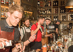 The world's best bartender, Jack McGarry, from New York (where he runs The Dead Rabbit bar, the best bar in the world 2016 ) is serving cocktails in Edinburgh this week. Here he is working in Devils Advocate just off the Royal Mile. All part of a five day Tales of the Cocktail event taking place in numerous venues across the city this week. Pictured: Jack McGarry (in red)<br /> <br /> <br /> &copy; Jon Davey/ EEm