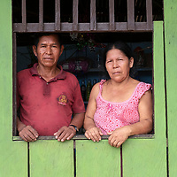 A couple poses for a photograph in the window of their home (which is also a small market) in the small community of San Francisco de Loreto on the Marañon River in the Peruvian Amazon.
