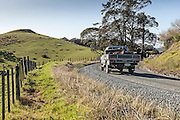 Ute driving around bend  on unsealed road in New Zealand