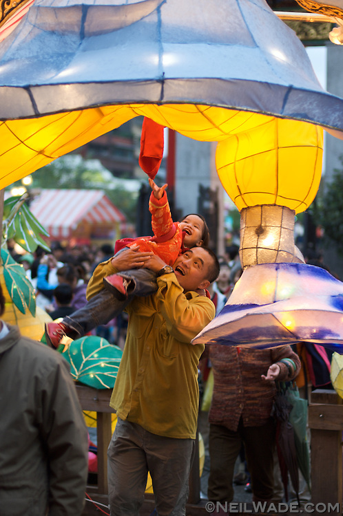 A father lifts his daughter to pull a lucky flag at Lungshan Temple, Chinese Lunar New Year 2007 in Taipei, Taiwan.