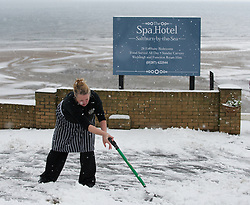 © Licensed to London News Pictures. 15/01/2013..Saltburn, Cleveland, England..As heavy snow falls on Saltburn the staff from the Spa Hotel come out to help clear say the snow...Photo credit : Ian Forsyth/LNP