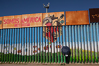 A woman in Playas de Tijuana stands along the border that separates Mexico and the United States, a surveillance camera ominously overhead. She is talking to a loved one through the fence. Often on weekends the US Border Patrol opens access to Friendship Park in Imperial Beach on the opposite side, so that family and friends unable to cross the border can share a moment together, even if it is through a metal barrier that only allows for fingertips to touch.