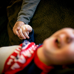 Home health care worker Sabrina Warner holds the hand of 9 year old Lucas Aldrich. Alissa Aldrich takes care of her 9-year-old son, Lucas, full time. Lucas has a life-limiting neuro disorder called Lissencephaly. Tuesday December, 06, 2016.