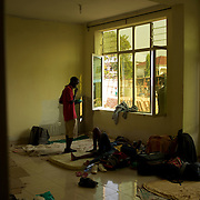 "A burundian university student, seeking shelter outside the US embassy in Bujumbura, talk to a college recovering from malaria, in a room of a vacant building close by. The students moved to the area in early May because, they claim, the US authorities ensure their security, after their university was closed amid anti-government protests. The government closed the university at the end of April, citing ""insecurity""."
