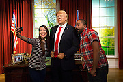UNITED KINGDOM, London: 18 January 2017 Visitors Helen Smith and Jason Holliday take a selfie with the wax figure of President Elect Donald J. Trump in the Madame Tussauds London's Oval Office section at its unveiling today. The London wax figure is one of four Trump figures created by Madame Tussauds globally, the others are in Washington D.C, New York and Orlando. Rick Findler / Story Picture Agency