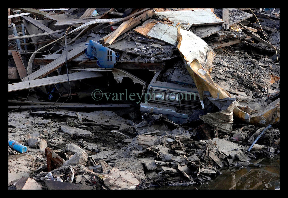 30th Sept, 2005. Hurricane Katrina aftermath, New Orleans, Louisiana. Lower 9th ward. The remnants of the lives of ordinary folks, now covered in mud as the flood waters remain. A car's headlights peer out from underneath a pile of rubble.