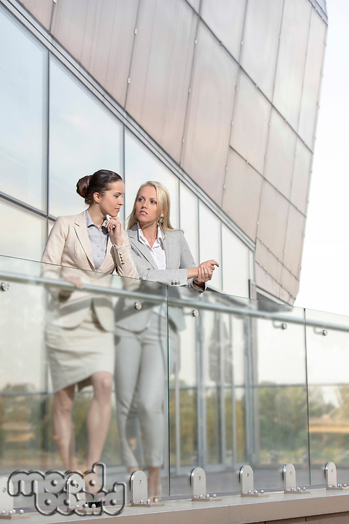 Full length of young businesswomen conversing at office balcony
