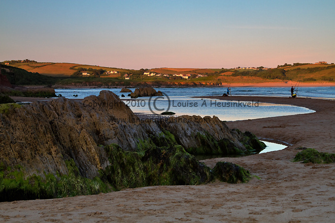 The beach at Bigbury-on-Sea at dusk, South Hams, Devon. Large rocks on the beach and a view toward the rolling countryside of Bantham Beach. Men are surf fishing in the late evening light.