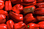 Fresh red Peppers group, stacked side by side in a farmers market.
