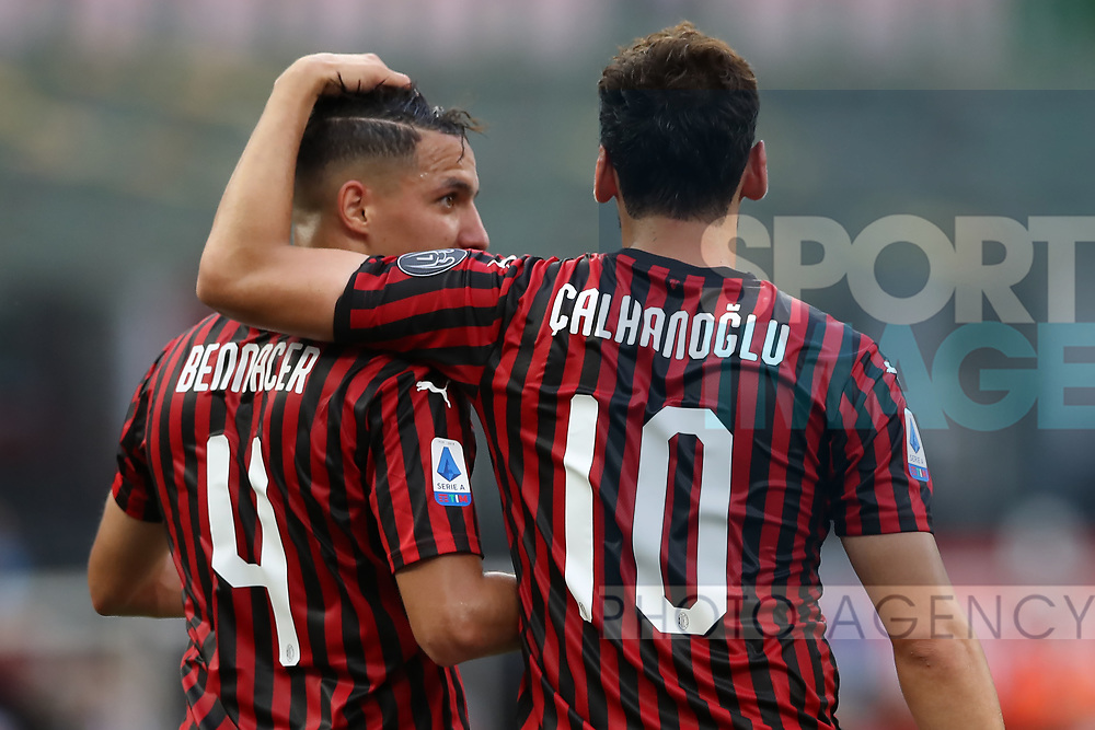 AC Milan's Turkish midfielder Hakan Calhanoglu celebrates with Algerian midfielder Ismael Bennacer after scoring form the penalty mark to give the side a 2-0 lead during the Serie A match at Giuseppe Meazza, Milan. Picture date: 28th June 2020. Picture credit should read: Jonathan Moscrop/Sportimage