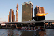 Tokyo sky tree under construction seen behind the Asakusa skyline as a sight seeing boat goes past, including the famous Flamme d'Or sculpture on top of the Asahi Beer Hall building.  When finished this telecommunications towewr will measure 634 metres from top to bottom making it the tallest structure in East Asia. Oshiage, Tokyo, Japan. December 29th 2010