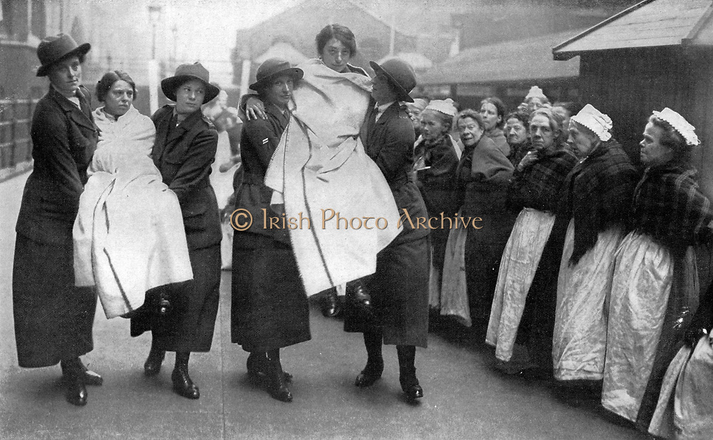 World War I, 1914-1918: British women fire fighters training at a workhouse. Elderly female residents watch the exercise. During the war women on the home front took over many jobs traditionally done by men.