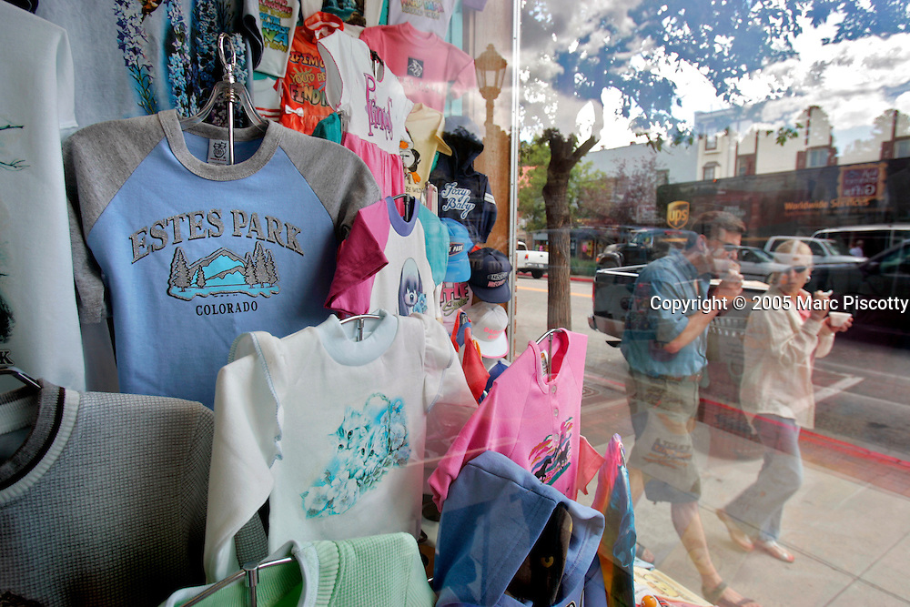 A pair of tourists walk past t-shirts on display in the window of the Estes Park Sweatshirt Center shop on West Elkhorn Avenue, the main street through Estes Park, one afternoon as they eat ice cream. Estes Park is the gateway town to Rocky Mountain National Park and has been criticized as a somewhat carnival-like atmosphere filled with fudge shops and t-shirt emporiums. Rocky Mountain National Park, established in 1915, on the other hand is a showcase of the grandeur of the Rocky Mountains and features peaks ranging from 8,000 to 14,259 feet tall and is home to elk, mule deer, bighorn sheep, black bears, coyotes and a wide range of birds, fish and smaller animals.  Rocky Mountain National Park is located in the north-central region of the U.S. state of Colorado. Rocky Mountain National Park features majestic mountain views, a variety of wildlife, varied climates and environments?from wooded forests to mountain tundra?and easy access to back-country trails and campsites. The park is located north-west of Boulder, Colorado in the Colorado Rockies, and includes the Continental Divide and the headwaters of the Colorado River in its land area.Rocky Mountain National Park encompasses approximately 265,770 acres (1,076 km²) of land in Colorado's northern Front Range. The park is split by the Continental Divide, which gives the eastern and western portions of the park a different character. The east side of the park tends to be dryer, with heavily glaciated peaks and cirques. The west side of the park is wetter and more lush, with deep forests dominating. The park contains 359 miles (578 km) of trails, 150 lakes, and 450 miles (720 km) of streams. The park contains over 60 named peaks higher than 12,000 feet (3,700 m), and over one fourth of the park resides above tree line. The highest point of the park is Longs Peak, which rises to 14,259 feet above sea level. Longs Peak is the only fourteen thousand foot peak in the park..(MARC PISCOTTY/ © 2005)