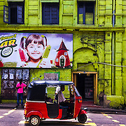 A red TukTuk drives past a green painted building in Slave Island Colombo Sri Lanka