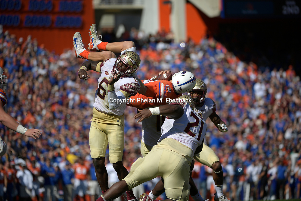 Florida quarterback Feleipe Franks (13) is upended by Florida State linebacker Matthew Thomas (6), defensive tackle Marvin Wilson (21) and linebacker Ro'Derrick Hoskins (18) on a quarterback keeper during the first half of an NCAA college football game Saturday, Nov. 25, 2017, in Gainesville, Fla. (Photo by Phelan M. Ebenhack)