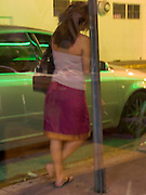 Young woman waiting alone by parked car at night.