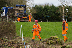 Denham, UK. 4 February, 2020. Engineers walk across land cleared for works for the HS2 high-speed rail link project. Behind other engineers prepare to unload a temporary roadway from a large truck. Planned works in the immediate vicinity are believed to include the felling of 200 trees and the construction of a roadway, Bailey bridge, compounds, fencing and a parking area. Credit: Mark Kerrison/Alamy Live News