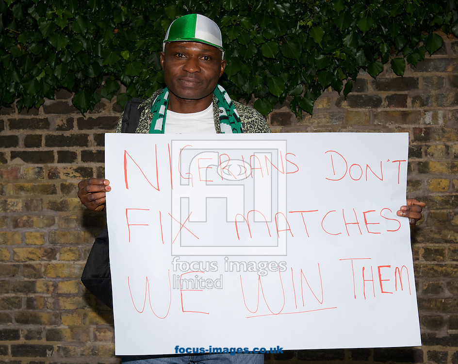 A Nigerian fan with a banner relating to the match fixing before the International Friendly match at Craven Cottage, London<br /> Picture by Alan Stanford/Focus Images Ltd +44 7915 056117<br /> 28/05/2014