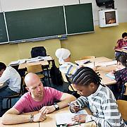 Nederland Rotterdam 23-09-2009 20090923 Foto: David Rozing  Serie over onderwijs, het Libanon Lyceum Kralingen,  openbare scholengemeenschap voor mavo, havo en vwo. Lesuur nederlands, leraar geeft uitleg aan leerling aan tafel. Orde houden, een vraag stellen.  , uitleg, uitleg geven, uitleggen, vaardigheden, vaardigheid, voor de klas staan, voortgezet, writing, young, Youth, zelfstandig werken, zin, zinnetje                                                       .Foto: David Rozing