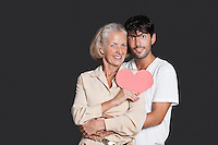 Young man embracing senior woman holding red paper heart against black background