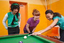 Girls playing pool in Youth Club. Cleared for Mental Health Issues.