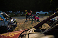 Two men roll their childrens' Big Wheels to the demolition derby track for the kids race at the Summitt County Fairgrounds, Thursday, July 26, 2016 in Tallmadge, Ohio.