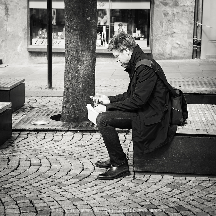 Man resting in central Bergen with envelope in his hand looking thoughtful on the screen of his telephon phone