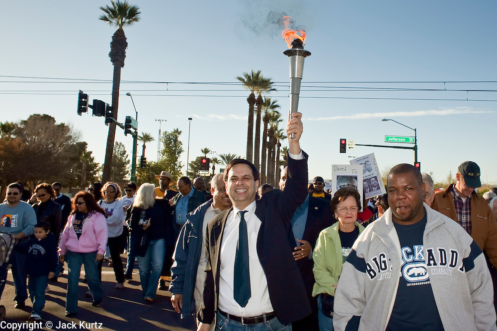 19 JANUARY 2009 -- PHOENIX, AZ: Phoenix Mayor PHIL GORDON carries a torch during the Phoenix Martin Luther King Jr. march. About 500 people marched three miles through Phoenix, Monday Jan. 19, in memory of Dr. Martin Luther King Jr. This year the march also marked Jan 20 inauguration of Barack Obama as the US President.   PHOTO BY JACK KURTZ