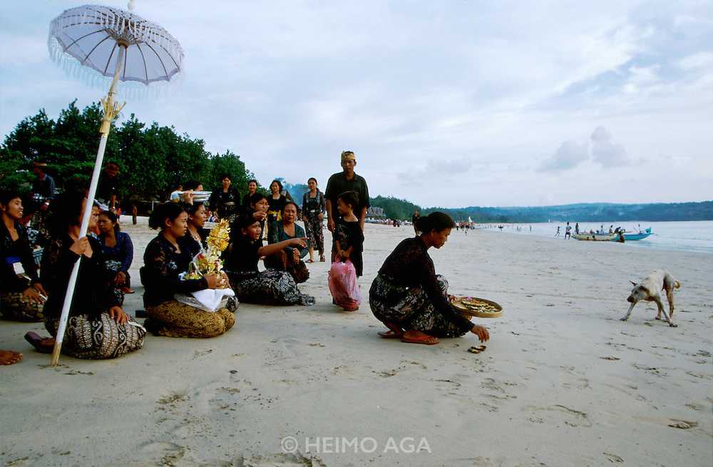 """Traditional Balinese Funeral. After a hindu ritual and the cremation of the body, family members fill the relics and ashes into an empty coconut shell, which is later carried in front of  a procession to the beach and dispersed at sea. One of Bali's ubiquitous stray dog (""""Cicik"""") is watching."""