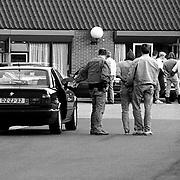 Arrestatie door een arrestatieteam van een van de Oosterbeek moordenaars, Piet Bakker word politieburo Huizen binnengebracht met een kap over zijn hoofd