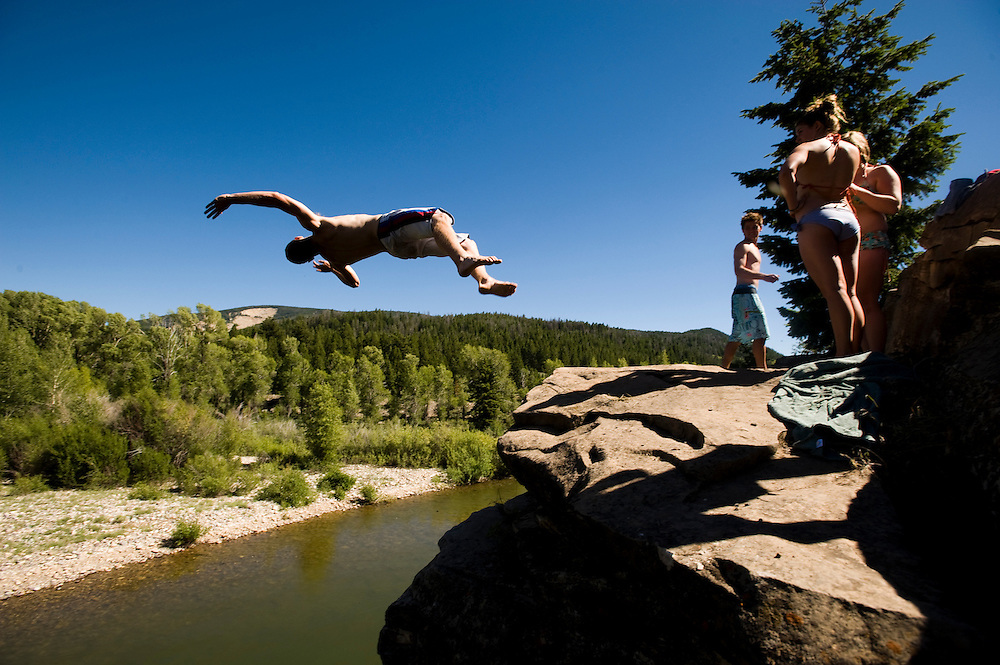 NEWS&GUIDE PHOTO / PRICE CHAMBERS.The perfect recipe for cooling off on a hot day, Jack Maguire does a backflip with a twist off of a cliff over the Gros Ventre River on Thursday.
