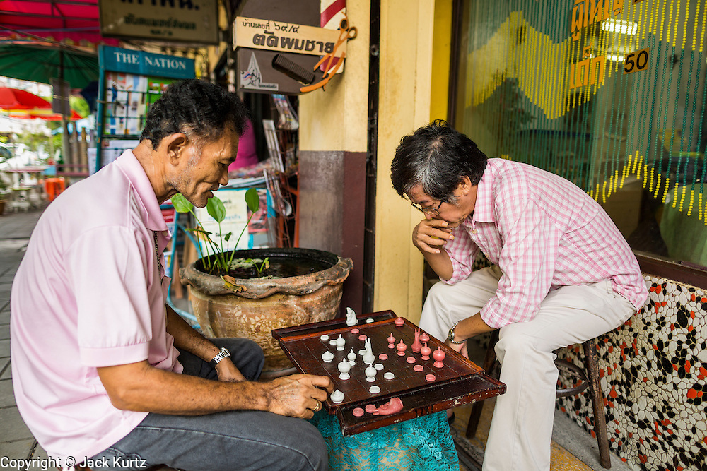 15 JULY 2014 - BANGKOK, THAILAND:    Men play chess on Samsen Soi 9 near the entrance to Wat Rachathiwat Ratchaworawihan. The temple has a large teak instruction hall, considered one of the finest teak buildings in Asia.   PHOTO BY JACK KURTZ