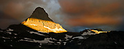 The rising sun catches the top of  Reynolds Mountain through parting storm clouds, in the Logan Pass region of Glacier National Park, Montana, USA
