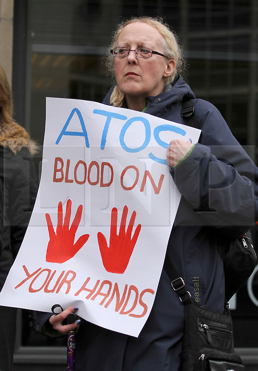 """© Licensed to London News Pictures. 19/02/2014. Manchester, UK. People protest in Manchester against ATOS Healthcare who carry out millions of """"fit-for-work"""" tests for sick and disabled benefit claimants on behalf of the UK Government. It is reported that the Government will terminate the contract with ATOS. Photo credit : Steve Purcell/LNP"""