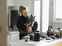 Woman holding cat standing in kitchen