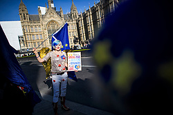 "© Licensed to London News Pictures. 14/02/2019. London, UK. Self titled ""EU Supergirl, an Anti Brexit campaigner, outside the Houses of Parliament in Westminster, on the day that MPs are due to take part in further debates and votes on Brexit. A series of amendments are being tabled to try to change the direction of Brexit, but a vote on a deal will not be held today as was originally planned. Photo credit: Ben Cawthra/LNP"