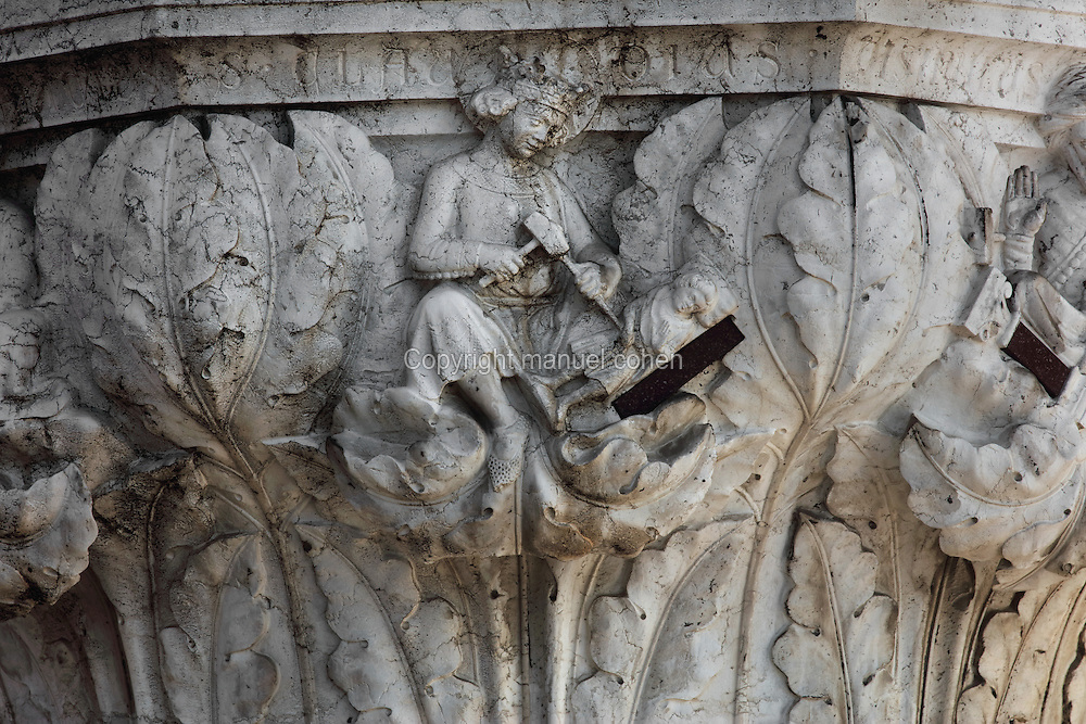 Sculpted capital of St Claudius carving a statuette out of stone using a hammer and chisel, carved 1340-1355, thought to be by Filippo Calendario, 1315-55, from Column 19, depicting 4 crowned saints sculpting, of the ground floor Piazzetta San Marco columns, on the Doge's Palace or Palazzo Ducale, begun 1340 and built in Venetian Gothic style, Venice, Italy. The palace has 2 arcades with 14th and 15th century capitals and sculptures, and a loggia above with a decorative brickwork facade. It was the residence of the Doge of Venice, the supreme authority of the former Republic of Venice, until the Napoleonic occupation in 1797, and is now a museum. The city of Venice is an archipelago of 117 small islands separated by canals and linked by bridges, in the Venetian Lagoon. The historical centre of Venice is listed as a UNESCO World Heritage Site. Picture by Manuel Cohen