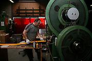 Fabrication de cloches, clochettes et de plaques d'immatriculation automobiles  chez Firmann SA à Bulle. Bei Firmann SA werden Glocken Metallstanzteile hergestellt