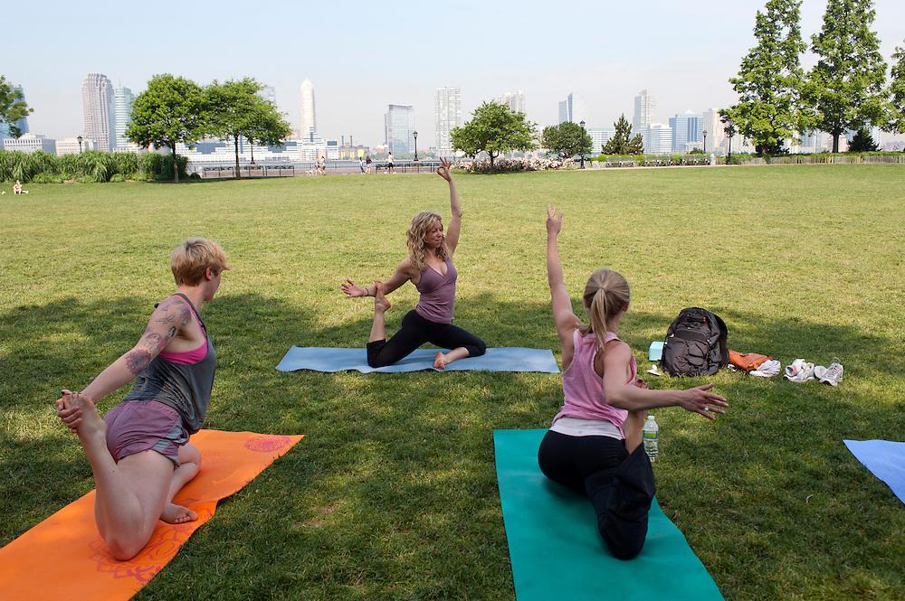 Yoga Lehrerin Donna Klimkiewicz (Mitte) gibt Yoga Klassen im Rockefeller Park am Hudson River. Links: Yvonne Adamek. New Jersey Skyline...Yoga in New York..Foto: Stefan Falke